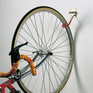 Крепление велосипеда к стене при помощи специальных крюков на стене.
